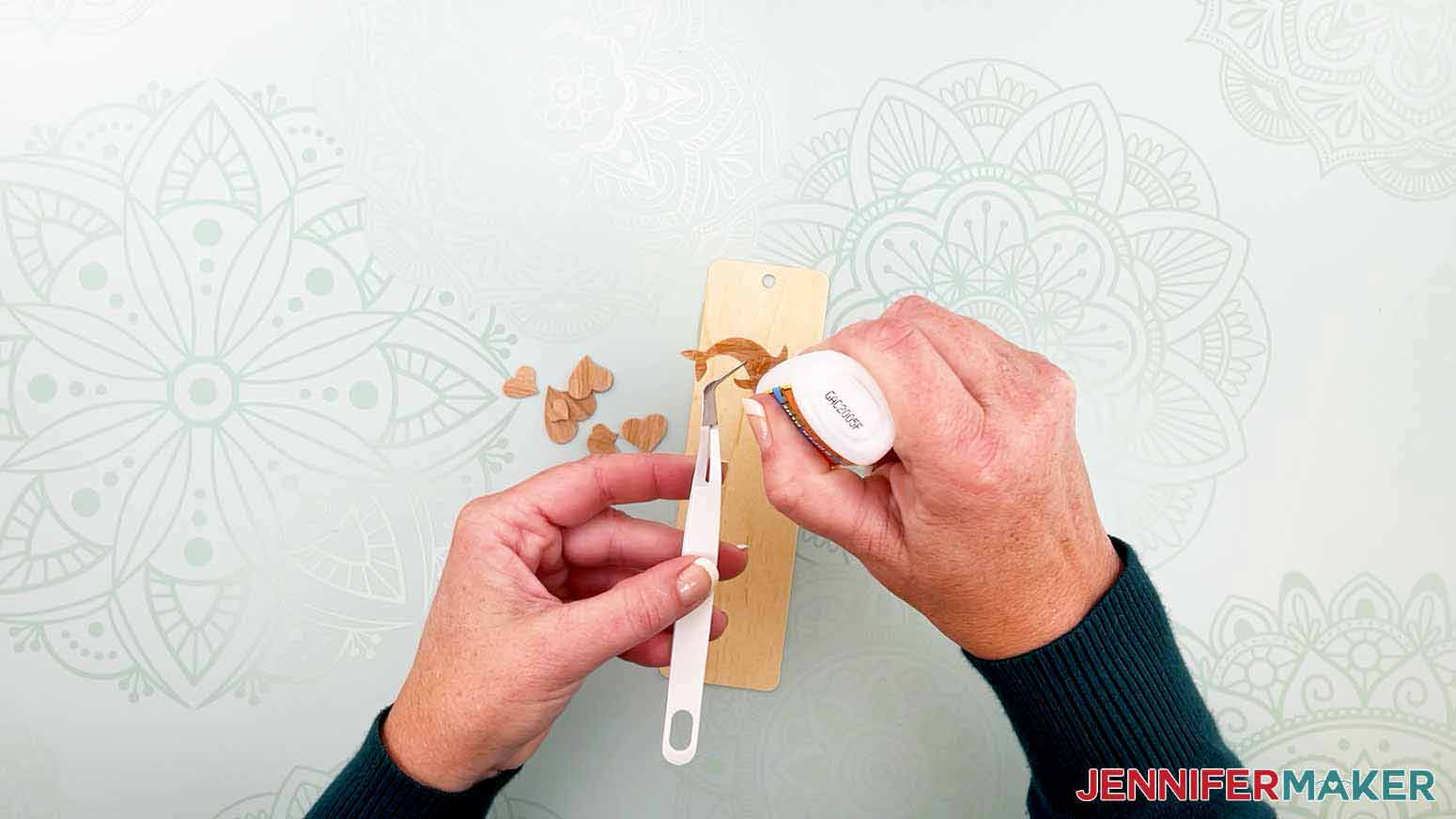 Use tweezers for small pieces and add glue for my wooden bookmarks project
