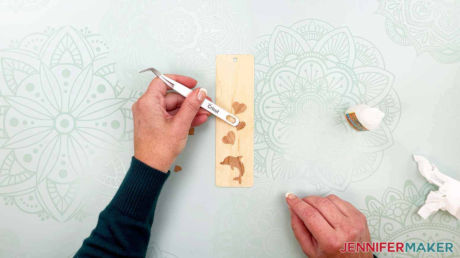 Use tweezers to place small pieces on a blank bookmark for my wooden bookmarks project