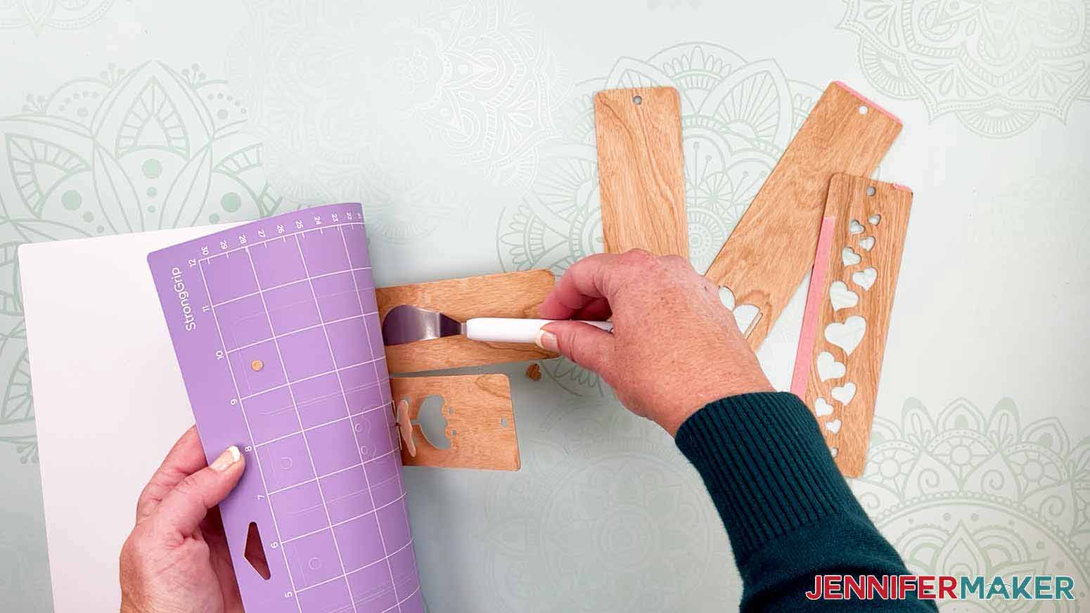 Use a scraper tool to help remove the veneer from the cutting mat for my wooden bookmarks project
